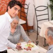 Young waiter serving senior couple in restaurant — Stock Photo