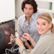 Woman fixing a television set — Stock Photo