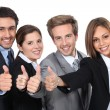 Four young professionals giving the thumbs up — Foto de Stock