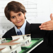 Boy dressed as a businessman in an architect's office — Stock Photo