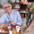Stock Photo: An old woman having breakfast with a younger woman