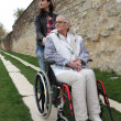 Young woman with elderly woman in wheelchair - Stock Photo