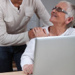 Son helping mother on laptop — Stock Photo #7906771
