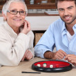 Young man playing dice with older woman — Stock Photo