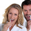 Woman and man brushing teeth — Stock Photo