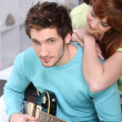 Young couple at home with a guitar — Stockfoto