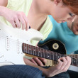 Stock Photo: Girl learning to play guitar