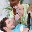 Young couple with a guitar and a microphone - Stockfoto