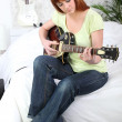 Young female guitarist at home — Stockfoto