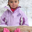 Little girl carrying a log through the snow — Stock Photo #7907988