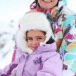 Mother and daughter sitting in snow — Stock Photo #7908006