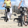Young man and woman riding bikes on the beach - Stock Photo