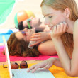 Three female teenagers with a laptop on the beach — Stockfoto