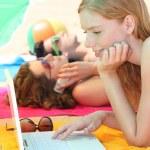 trzy nastolatki kobiece z laptopa na plaży — Zdjęcie stockowe