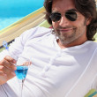 Man drinking cocktail near the pool — Stock Photo