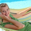 Blond woman with mobile telephone laying in hammock — Foto Stock