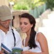 Couple reading their guide during an holiday trip. - Stock Photo