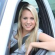 Young woman leaning out of car window — Stock Photo #7909478