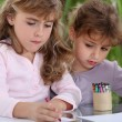 Stock Photo: Little girls drawing with crayons