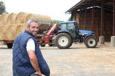 Famer stood by hay barn — Stock Photo