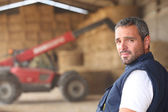 Farmer posing in front of a tractor — Stockfoto