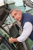 Portrait of a farmer climbing on tractor — Stock Photo