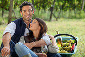 Romantic man and woman picking grapes and drinking wine — Stock Photo