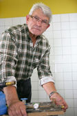 Elderly man gluing parts together — Stock Photo