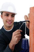 Handsome bricklayer fixing bell on brick wall — Stock Photo