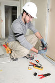 Man snipping wall wiring — Stock Photo