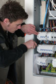 Electrician checking a distribution board — Stock Photo