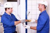 Dos ingenieros eléctricos machos comprobar la potencia de la fuente — Foto de Stock