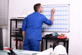 Factory worker marking date on calendar — Foto Stock