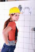Tradeswoman examining a blueprint — Zdjęcie stockowe