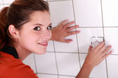 Woman fitting an electrical outlet in bathroom — Stock Photo