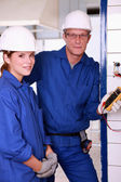 Young female apprentice electrician — Stock Photo