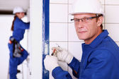 Eletricista de ligação a uma tomada de parede — Foto Stock