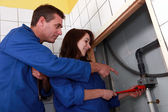 Plumber instructing his apprentice — Stock Photo