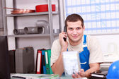 Man on telephone checking a plumbing part — Stock Photo