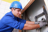 Young plumber fitting pipes — Stock Photo