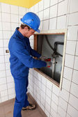 Plumber working in a tiled room — Stock Photo