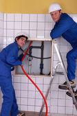 鉛管工のタイル張りの部屋での作業 — ストック写真
