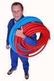 Studio shot of plumber with reels of tube — Stock Photo
