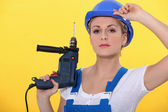 A blonde woman wearing an overall posing with a drill and adjusting her hel — Stock Photo