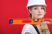 Portrait of lovely blonde craftswoman holding ruler against red background — Stock Photo