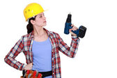 Tradeswoman holding up her electric screwdriver — Stock Photo