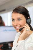 Mulher usando um fone de ouvido de telefone em um escritório — Fotografia Stock