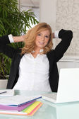 Blond woman stretching at her desk — Stock Photo
