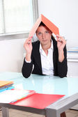 Young woman hiding under a file — Stock Photo