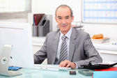 Senior businessman working at a computer — Stock Photo